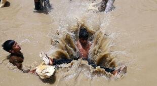Dzieci chłodzą się w błotnistej wodzie (PAP/EPA/SHAHZAIB AKBER)